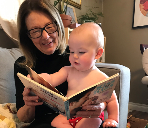 Baby Fern plays with a board book while being read to