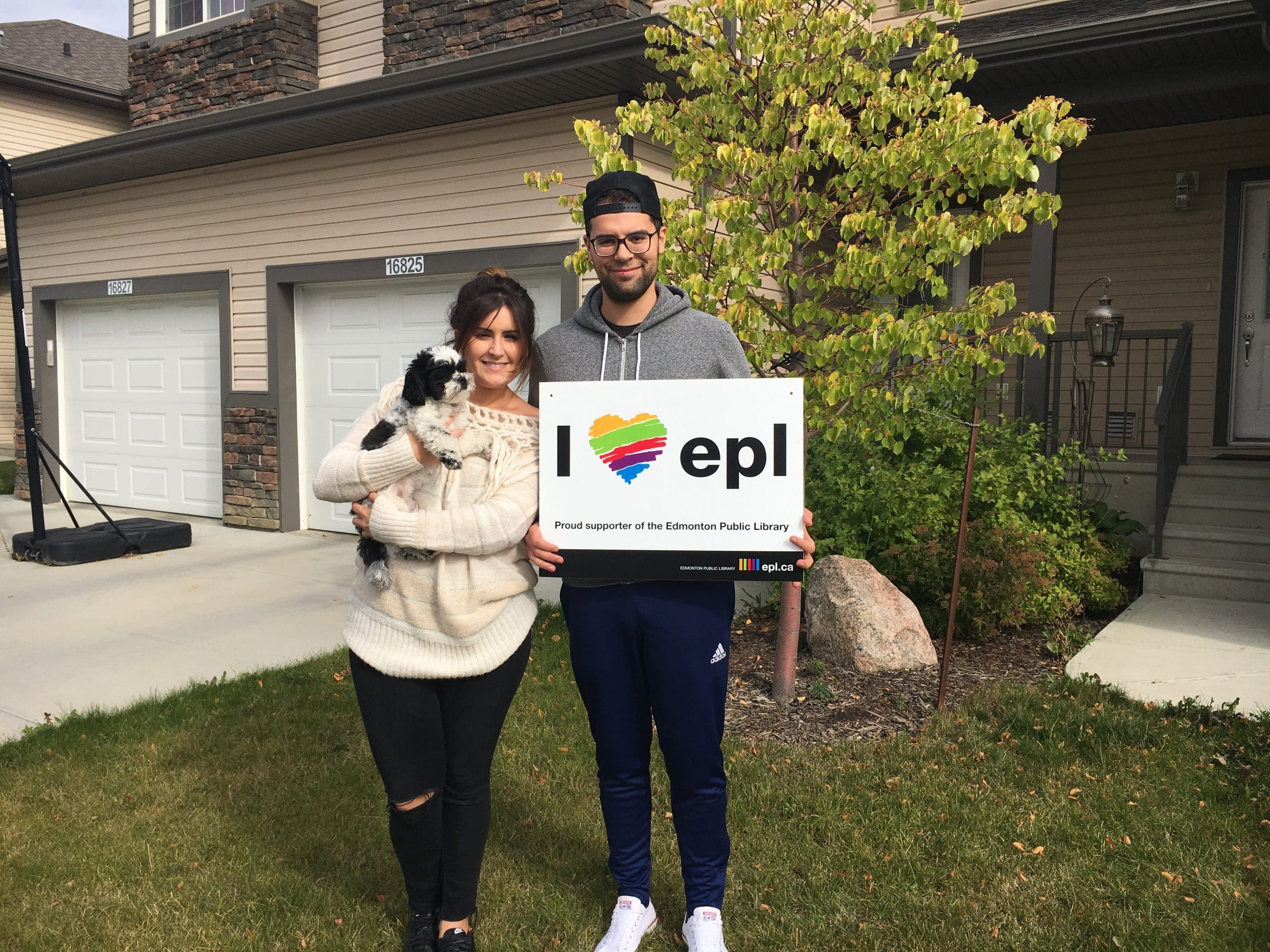 Briana, Mitch, and Zoey proudly holding an EPL lawn sign in front of their house