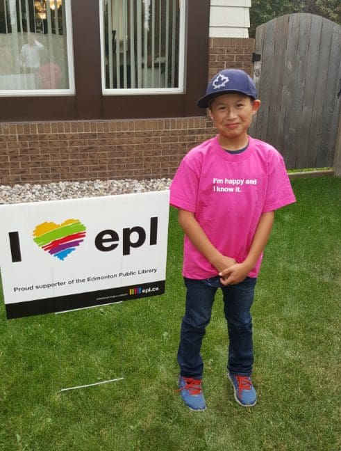 Child wearing an EPL tshirt and standing in front of an EPL lawn sign