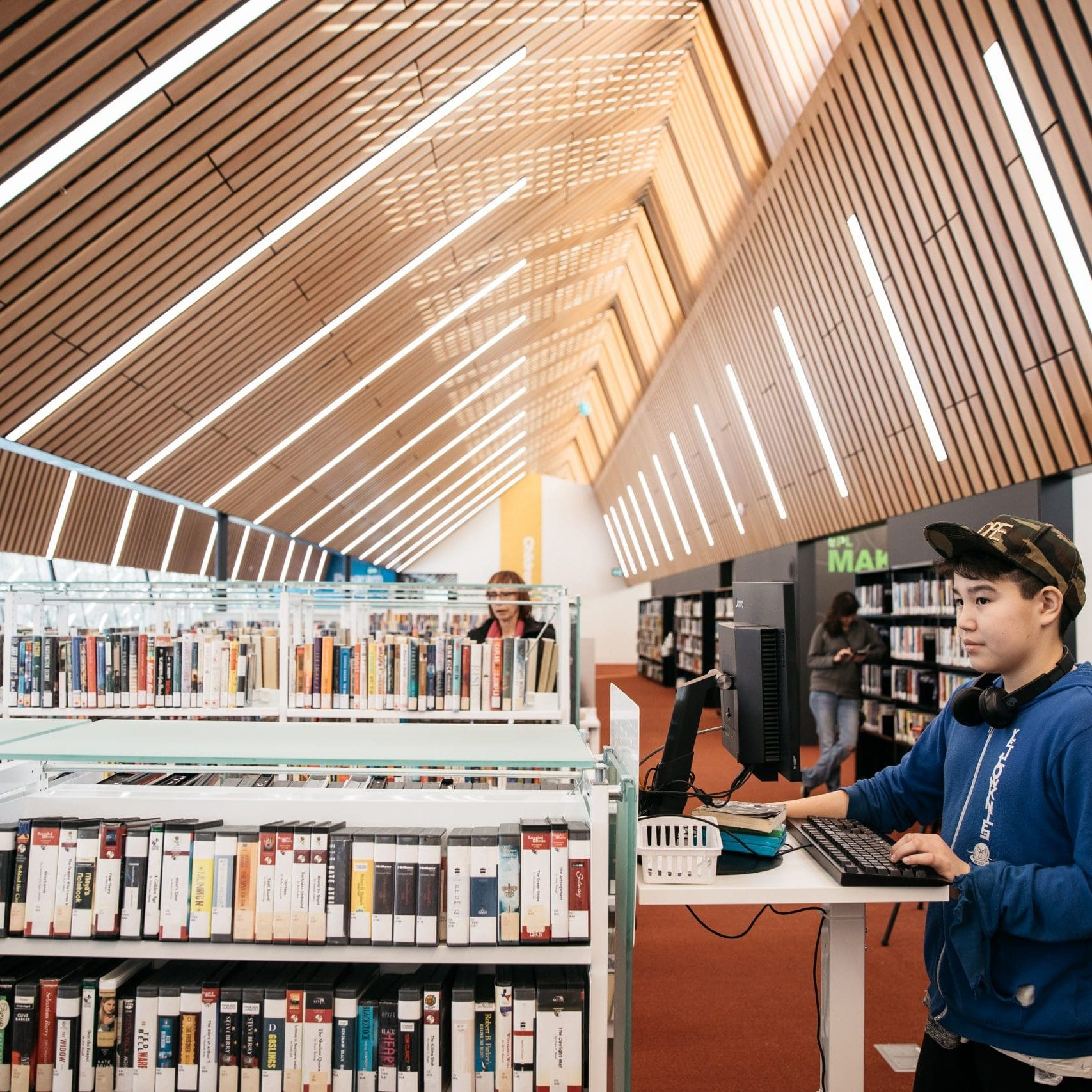 Customer at Capilano Branch stands beside book stacks and uses a computer