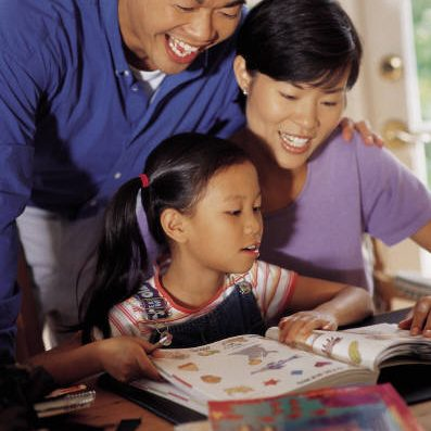 A family sitting at a table using a Family Learning Kit